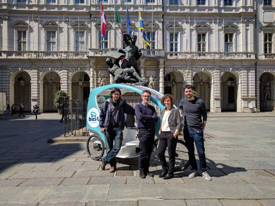 I soci di Bici-t. Vittorio Bianco, Giuseppe Piras, Elisa Gallo, Diego Enrico Panzetta di fronte al Palazzo Civico e al monumento al Conte Verde.